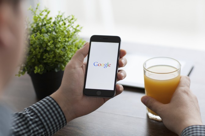 Man holding iPhone 6 mobile phone with Google on the screen